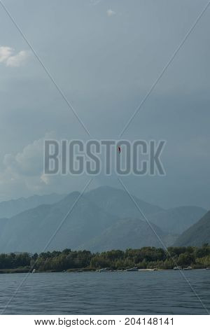 paragliding above lake water in front of mountain on a cloudy day