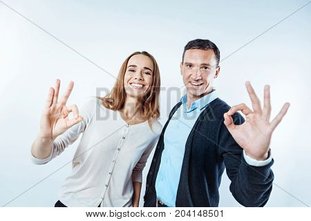 Everything is ok. Waist up shot of relaxed employees smiling while standing next to each other and showing an ok sign into the camera.