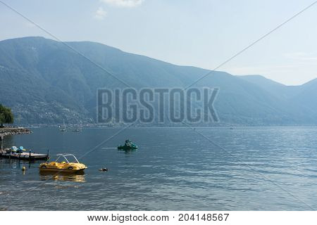 Pedalo Boat on lago maggiore lake in switzerland with moutnain view