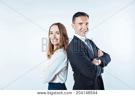 Positivity is the key to success. Waist up shot of friendly business coworkers looking into the camera with cheerful smiles on their faces while both posing with their hands crossed.