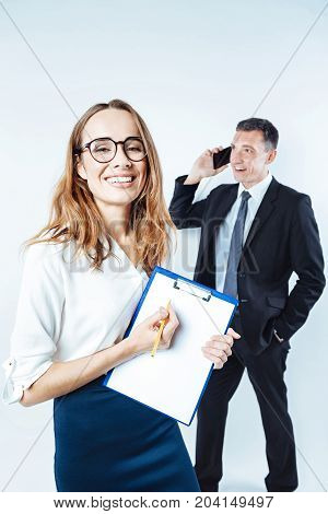 Have you seen. Joyful young woman grinning broadly while standing with a clipboard and pointing toward a written information with her male coworker talking in the background.