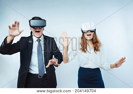 Unreal feeling. Cropped shot of amazed office workers gesturing while getting new experience and wearing a virtual reality goggles.