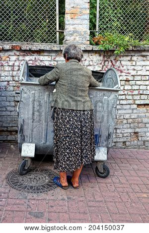 hungry beggar old woman looking for food in a garbage can