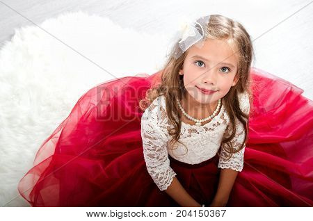 Adorable smiling little girl child in princess dress sitting on the floor