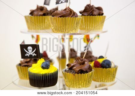 Cupcakes on stand in yellow and black colors pirate theme for kids birthday party