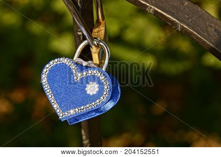 blue padlock in the form of a heart on iron bars