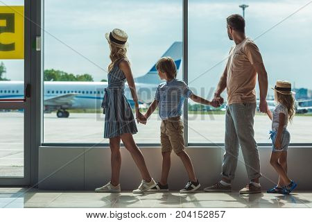 Family Looking Out Window In Airport