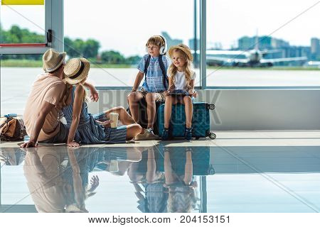 Parents And Kids Waiting For Boarding In Airport