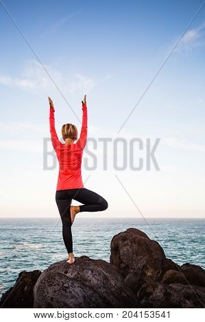 Yoga girl meditating in yoga vrksasana tree pose silhouette at the ocean beach and rock mountains. Motivation and inspirational fit and exercising. Healthy lifestyle outdoors in nature fitness concept.