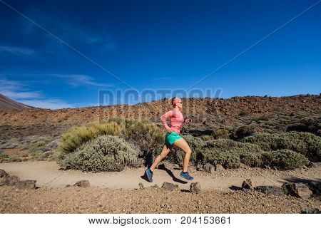 Woman running in mountains on sunny summer day. Beauty female runner jogging and exercising outdoors in nature trail running training on rocky trail footpath on Tenerife Canary Islands