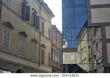Parma (Emilia Romagna Italy): old and modern buildings in the Cesare Battisti square. Reflections.