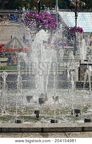 fragment of a city fountain with splashes and water on a sunny day