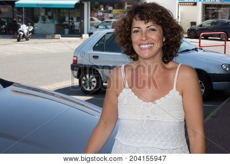Cheerful Woman Forties In Street With Parking Car