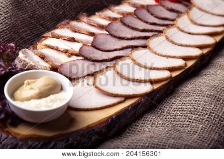 Cut pieces of smoked pork, veal and pork brisket with mustard and horse-radish on wooden board
