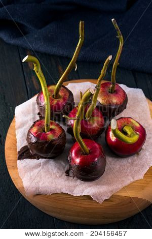 Apples in Black chocolate coating with sticks. Dessert for Halloween