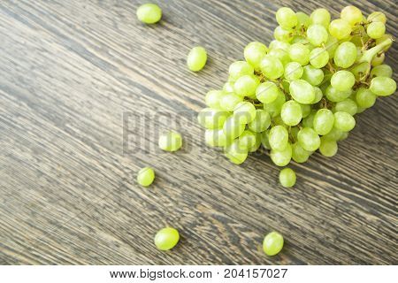 Brunch of green grapes on wood background.  Fruits of autumn