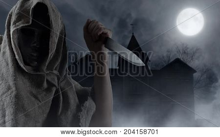 Hooded man with big knife . Abandoned wooden house in the moonlit night . Halloween background.