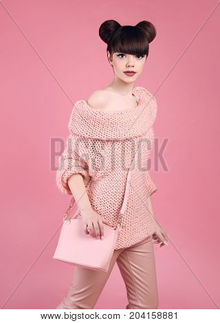 Fashion studio teen look style with casual handbag. Fashionable young girl wears wool sweater and leather pants posing isolated on pink background.