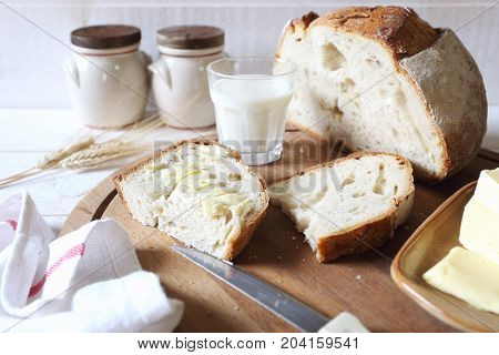 French sourdough bread butter and glass of milk on wooden chopping board