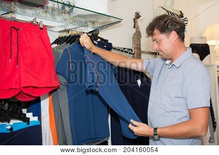 Happy Man Choosing New Clothes In Store