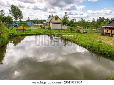 Wooden village house with outbuildings and small pond in summertime