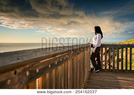 Woman standing at Hallett Cove boardwalk and looking into the sea at sunset South Australia