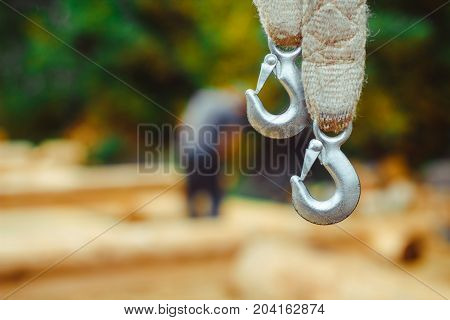 End of swinging rope hang on metal construction in a park. Rough rope end in metal circles and safety snap hook