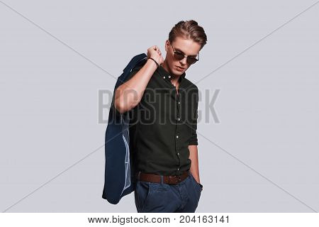 Charming young man. Good looking young man in eyewear carrying jacket on shoulder while standing against grey background