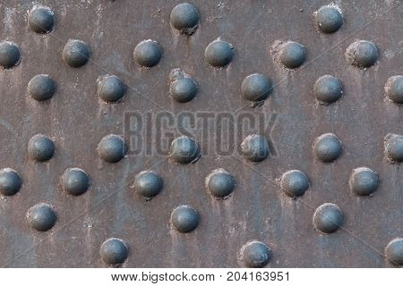 Rusty metal surface with hemispherical texture. Background texture