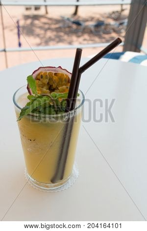 A glass of passion fruit smoothie on table at beach cafe.