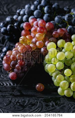 Variety of three type fresh ripe grapes dark blue, red and green. Close up over black metal ornate background.