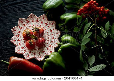 Useful antioxidant rosehip and lying on a platter on a dark background. Framed in ash , red and green . Healthy eating during deficiency