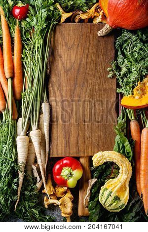Variety of autumn harvest vegetables carrot, parsnip, chard, paprika, hokkaido pumpkin, porcini and chanterelles mushrooms with empty wooden cutting board. Fall harvest concept. Top view with space
