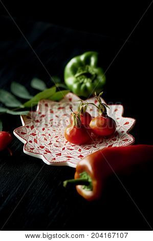 Useful antioxidant rosehip and lying on a platter on a dark background. Framed by red and green peppers. Healthy eating during the vitamin deficiency