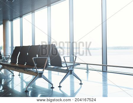 Empty airport terminal waiting area with chairs. passenger seat in Departure lounge for see Airplane, view from airport terminal. transport and travel concept
