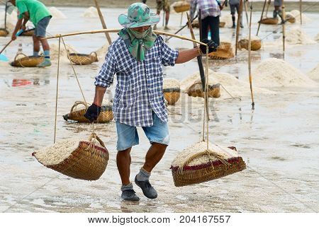 HUAHIN, THAILAND - MAY 13, 2008: Unidentified man carries salt at the salt farm in Huahin, Thailand. Salt production is one of the main industries in Huahin area it brings modest income to many local families.
