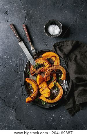 Roasted sliced pumpkin with balsamic sauce, greens and sea salt. Served on vintage metal tray with textile napkin and cutlery over black texture background. Top view with space