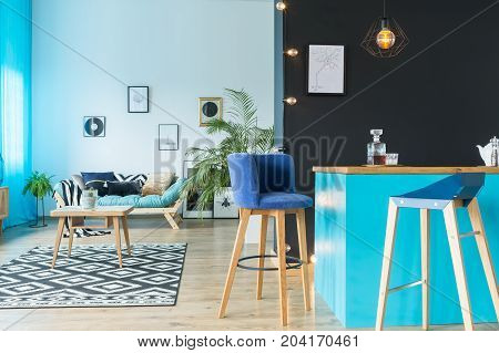 Blue suede barstool at kitchen island against black wall in multifunctional room