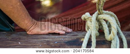 Fisherman`s Hand With Fishing Net In The Background. Wet And Wrinkled Hand Leaning On A Wooden Boat