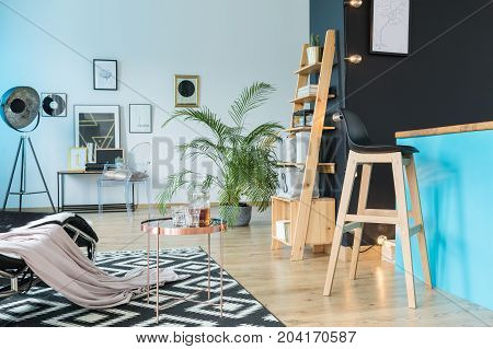 Spacious relax room with barstool at kitchen island and wooden shelf on black wall