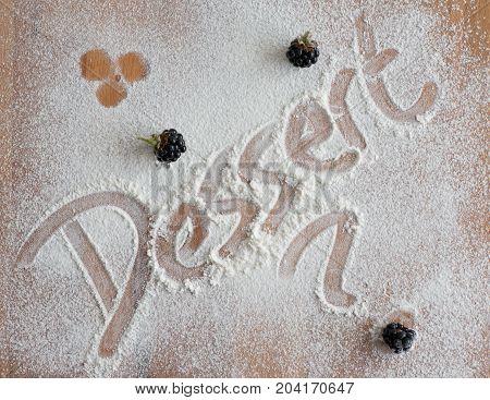Dessert written in caster sugar on a wooden chopping board.