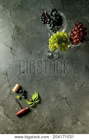 Variety of three type fresh ripe grapes dark blue, red and green in different laying wine glasses with old corkscrew and green leaves over black texture background. Top view with space.
