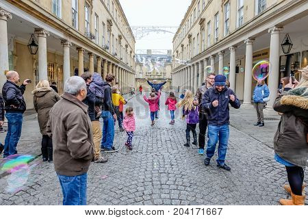 Bath UK - December 18 2016: unidentified people walk through the courtyard of the historic Bath Abbey in Somerset Bath city United Kingdom.