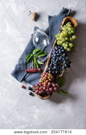 Variety of three type fresh ripe grapes dark blue, red and green in wooden bowl with empty laying wine glass, old corkscrew and green leaves over gray texture background. Top view with space.