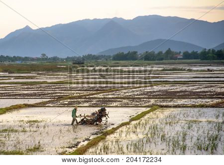 Ploughing paddy field with tractor machine against the background of mountains
