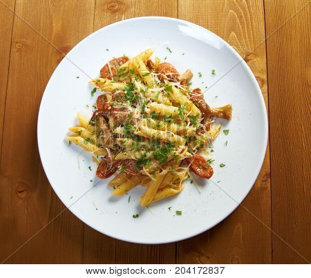 Italian Penne rigate pasta with sausage perish close up homemade meal
