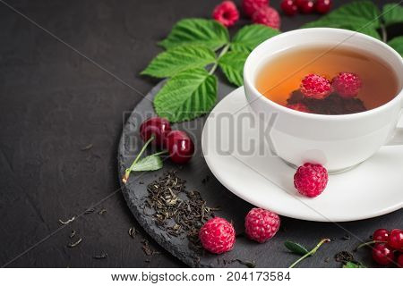 Berry tea and ripe raspberry cherry currant on a black background.