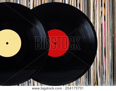 Two black vinyl records with color labels in front of pile of many close standing vinyl disks in old color covers over black background studio shot front view closeup