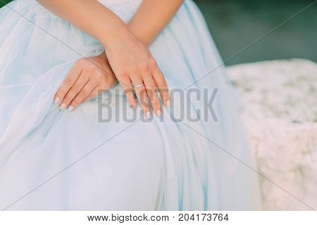 hands of a girl with an engagement ring on a white dress
