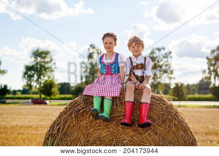 Two kids in traditional Bavarian costumes in wheat field. German children sitting on hay bale during Oktoberfest. Boy and girl play at hay bales during summer harvest time in Germany